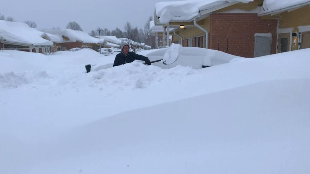 man med skyfflar snö utanför hus i bostadsområde, skyms nästan helt av enorma snödrivor täckte med nysnö.