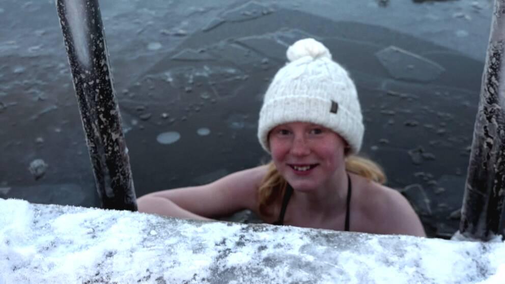 I bild är en tjej i 12 årsåldern som vinterbadar och har en mössa på sig.