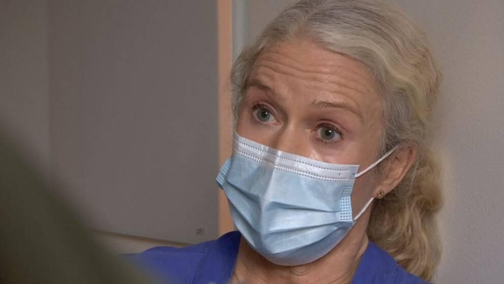 Ljushårig kvinna med munskydd syns titta åt vänster i bild.