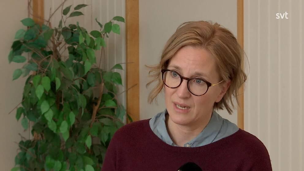 en kvinna med glasögon intervjuas inne på ett kontor