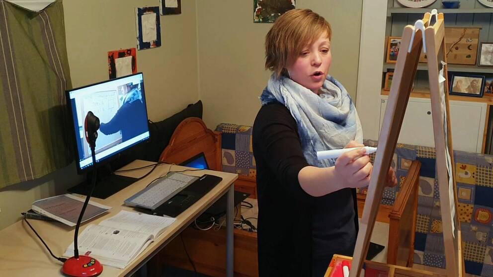 kvinna står framför kamera och dator och anteckningar på stående anteckningsblock
