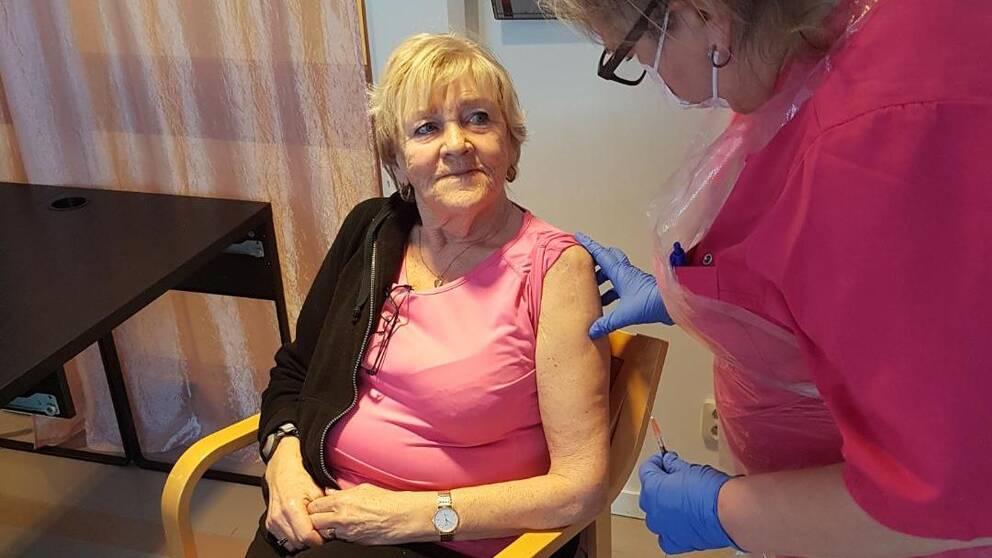 Blond kvinna klädd i rosa tröja och svarta byxor sitter i en stol En annan kvinna står bredvid och ska ge en vaccinationsspruta i vänsterarmen på hon som sitter i stolen.