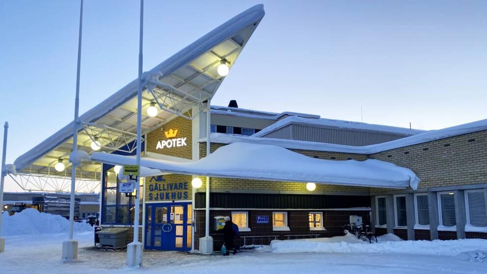 Stor byggnad i gult tegel med snö på taket. Ovanför dörren står det Gällivare sjukhus och Apotek.