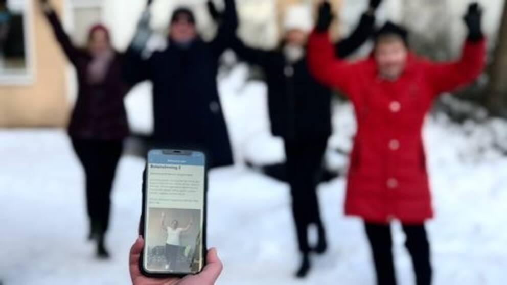 Mobil syns i förgrund med hälsoappen framme på skärmen där en person visar en rörelseövning. I bakgrunden syns konturer av människor som härmar övningen.