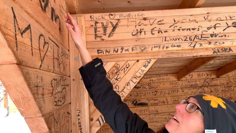 Sofia Tiger, föreståndare Naturrum, visar SVT:s reporter hur besökare skrivit sina namn och social medier på insidan av slogboden.