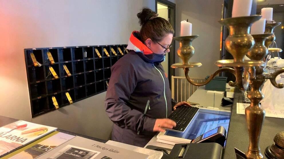 Malin Zetterman, restaurangägare i Älvdalen står vid datorn i en hotell-lobby.