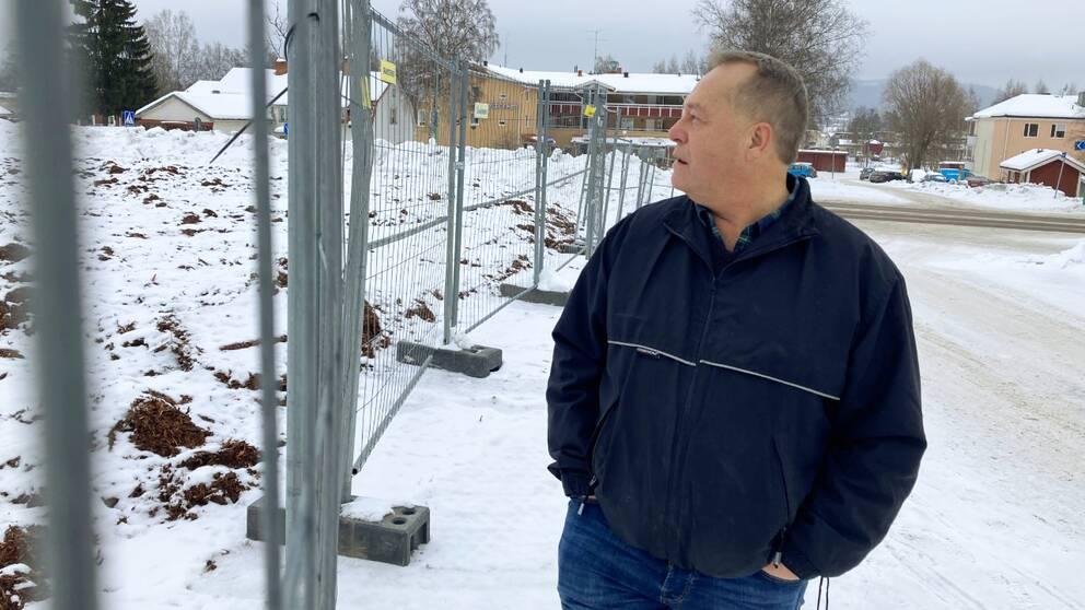 Magnus Hedni står bakom ett stängsel och blickar ut över platsen där hans gamla matbutik låg i Järvsö.