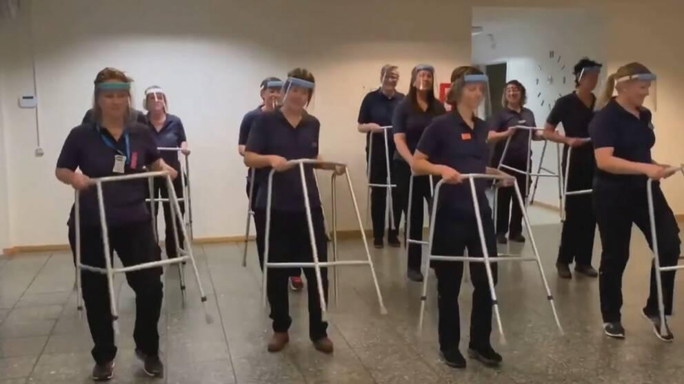 Bilden föreställer flera människor med mörkblå arbetskläder och visir. Framför sig håller de i varsin gåstol.