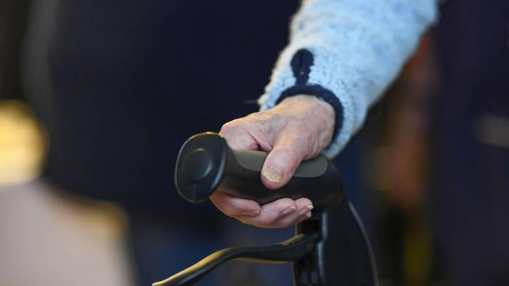 Arkivbild på en äldre person som håller i en rollator.