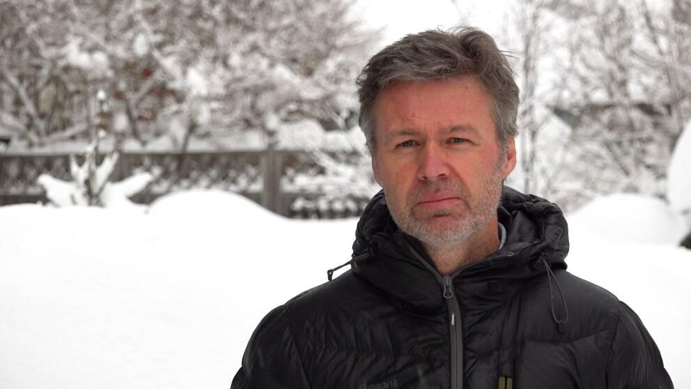 Smittskyddsläkare Stephan Stenmark står utomhus med oskarp snö i bakgrunden