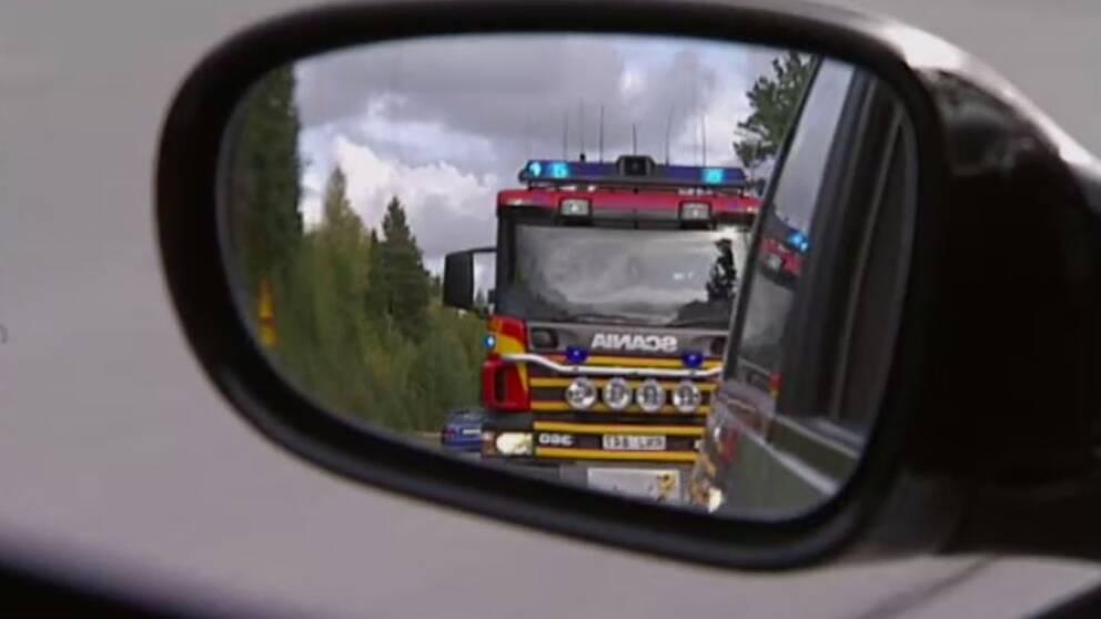 En brandbil syns genom en sidobackspegel.