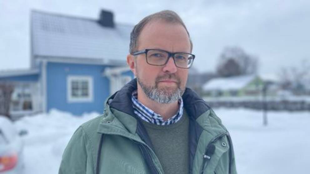 Mathias Sundin står utomhus framför ett blått hus. Han har en grön jacka och blå-vit rutig skjorta.