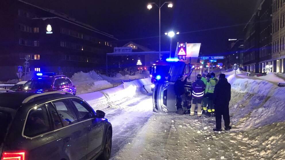 En mindre bil ligger på ena sidan på en snöig väg.