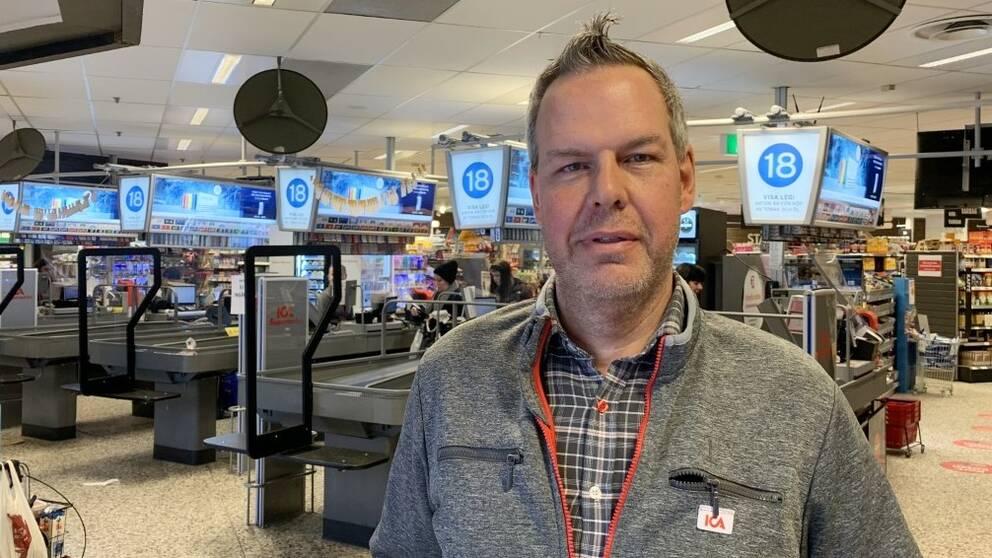 En man i gråa arbetskläder står framför kassorna på en ica-butik och tittar in i kameran.