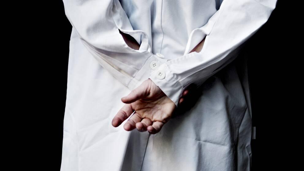 läkare i vit rock fotograferad bakifrån