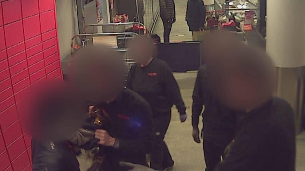Övervakningsbild som visar butikspersonal som konfronterar en person som försökt stjäla en salami i mataffären. De står efter kassorna och en från butiken har tagit tag i kragen på tjuven. De inblandade personerna är anonymiserade.