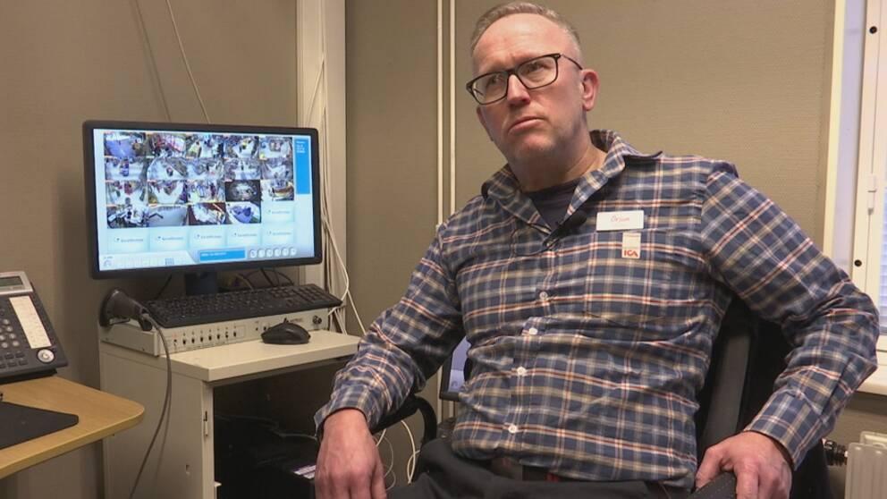 Handlare Örjan Josefsson sitter framför en datorskärm som visar övervakningsbilder från hans butik. På skärmen syns flera mindre rutor på olika gångar mellan varohyllorna i butiken.