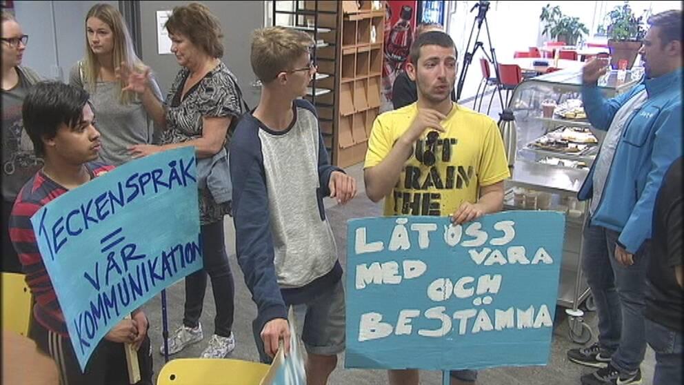 folk som tecknar och håller i protestplakat