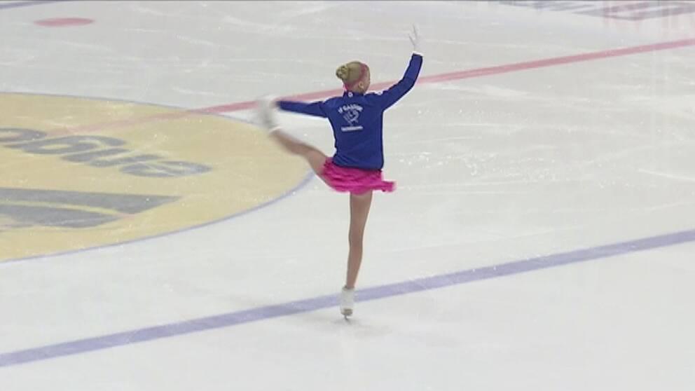 flicka med blont hår blå jacka och rosa kjol gör en piruett på en isrink
