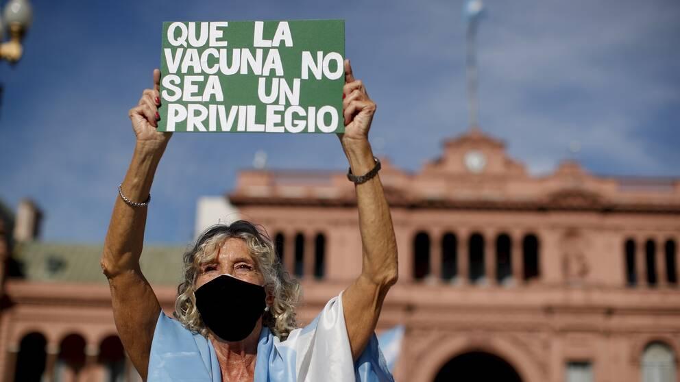 """""""Vaccin får inte vara ett privilegium"""", står det på ett av plakaten bland demonstranterna utanför regeringshögkvarteret i Buenos Aires."""