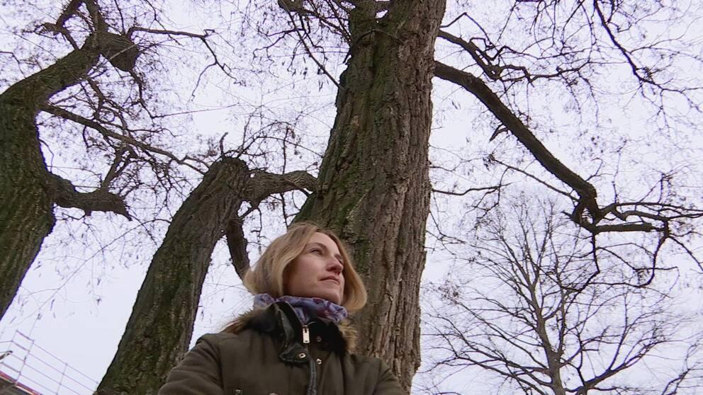 Sissel står lutad mot ett träd och man ser de nakna trädgrenarna ovanför.