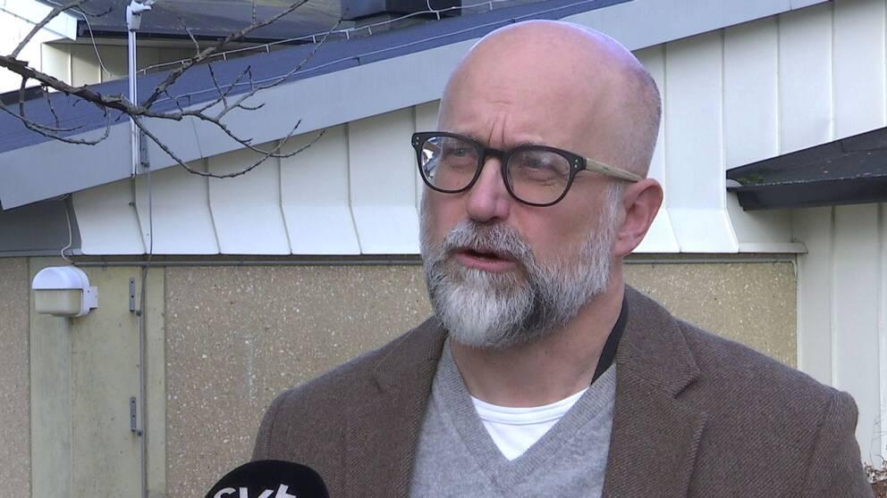 Bild på skallig man med grått helskägg. Mannen har svartbågade glasögon, brun kavaj, grå tröja.
