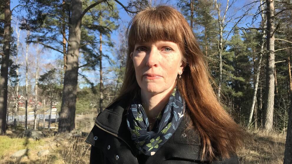 Lena Dahlberg docent vid högskolan står ute bland träd i solskenet.