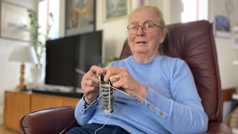 Karin Stråle sitter i en brun fåtölj och stickar på en strumpa.
