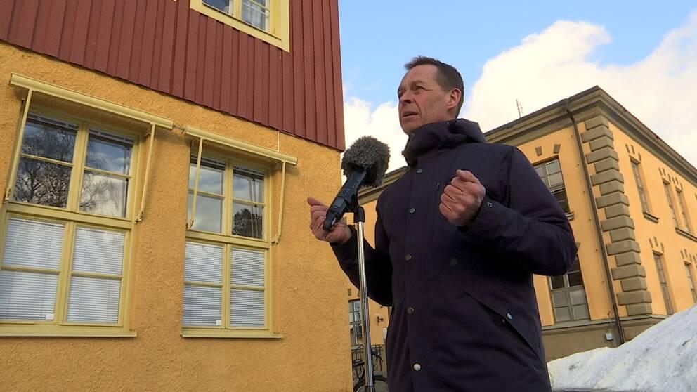 Man i blå jacka står vid ett mikrofonstativ. Tittar åt vänster. Bilden är tagen lite underifrån med två gulröda hus i bakgrunden.