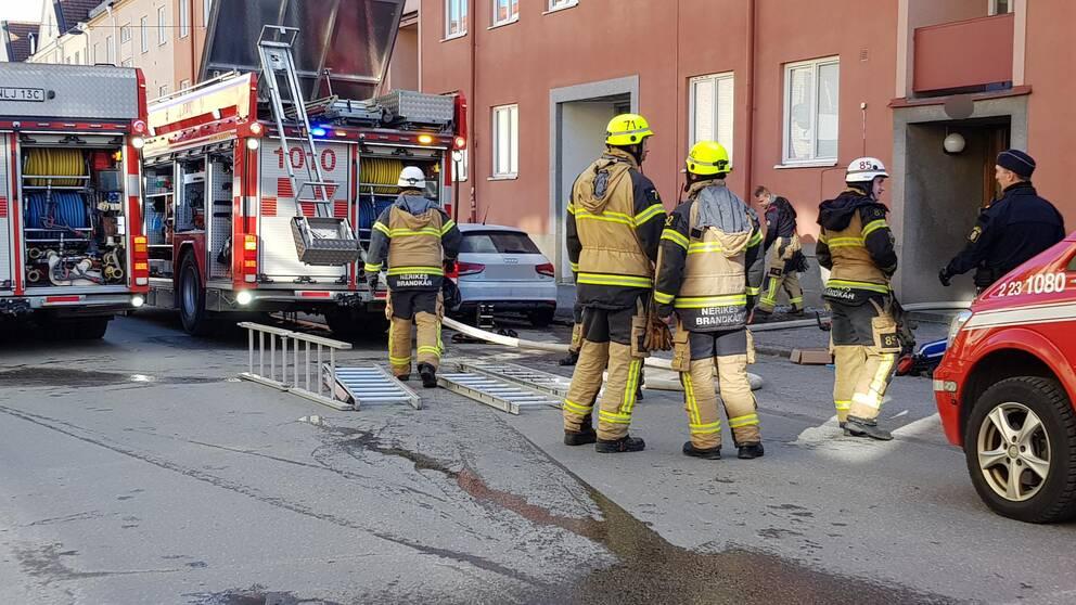 Räddningstjänstens personal och bilar utanför en lägenhet i örebro.