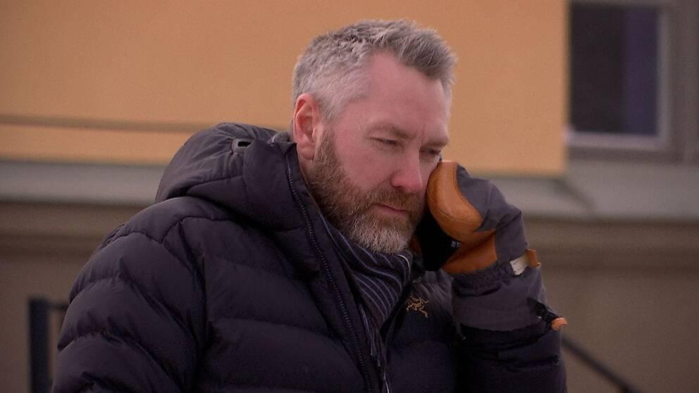 gråhårig man med skägg, klädd i mörk dunjacka står och pratar i telefon.