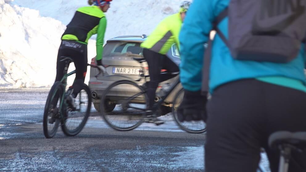 Tre män cyklar runt ett krön