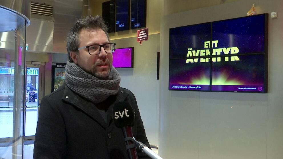 """man i glasögon och halsduk i biofoajé med tv med texten """"ett äventyr"""" i bakgrunden"""
