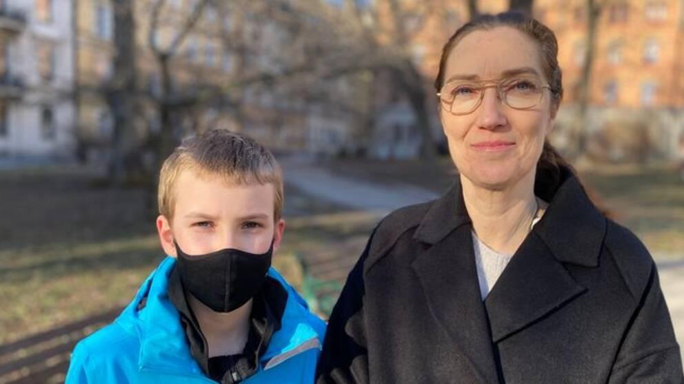 Linus har en blå jacka och ett svart munskydd på sig. Bredvid står hans mamma Sarah Jefford, hon har en svart jacka och glasögon. De är i fokus medan bakgrunden är lite suddig.