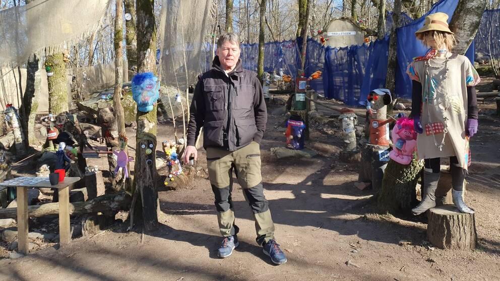 Lars Brandin i svart jacka framför sin trollskog, full med fantasifulla troll i olika storlekar.