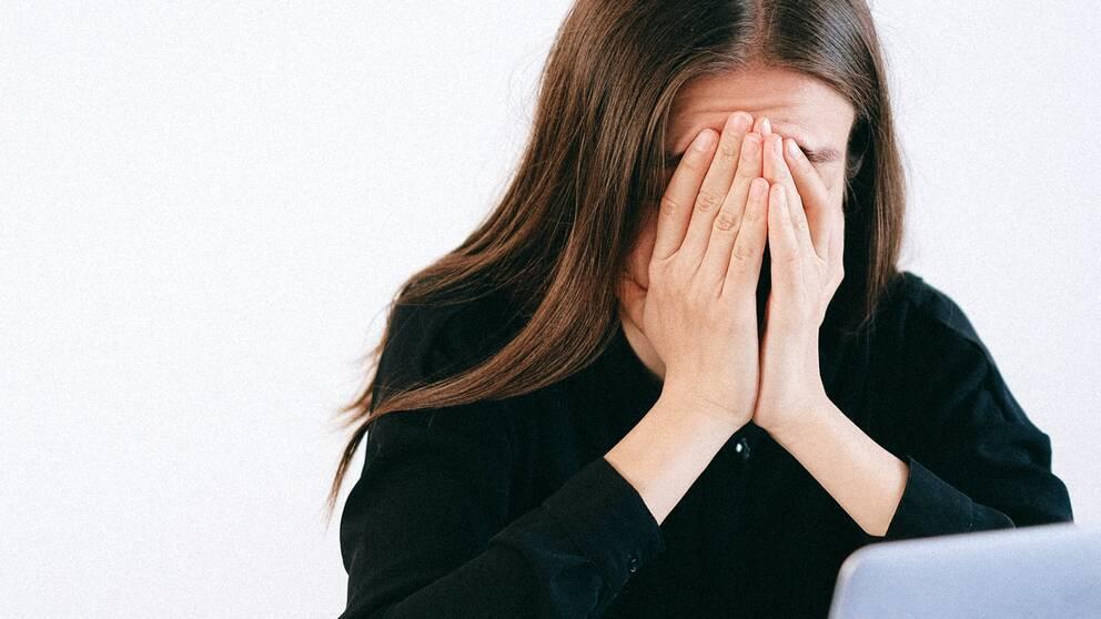 Person håller händerna framför ansiktet.