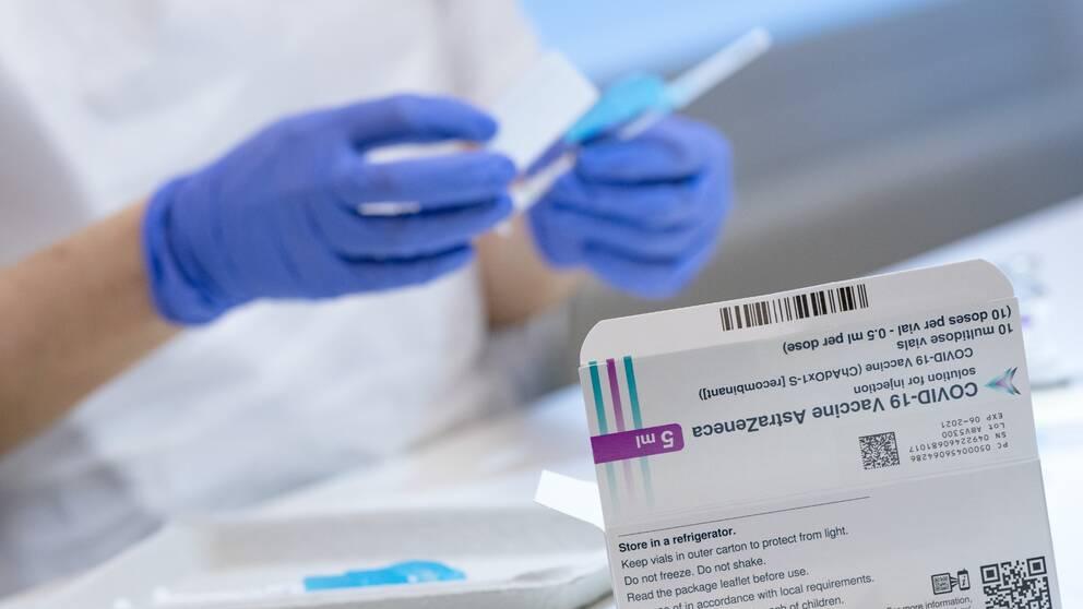 sjukvårdspersonal med plasthandskar och vaccinspruta, i förgrunden en ask från Astra Zeneca