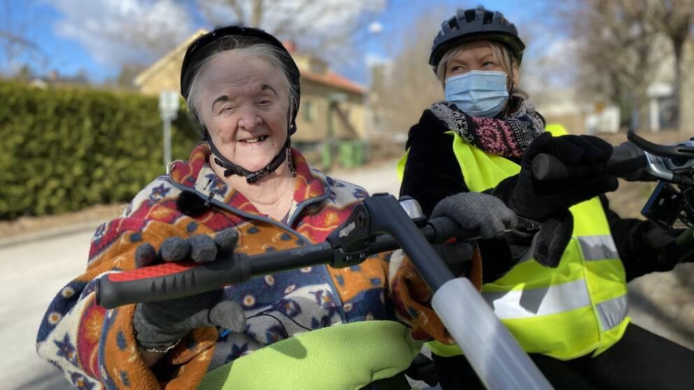 Halvbild på 90-åriga Kerstin Rause och Rose Andersson som jobbar på Rosengårdens äldreboende. Båda har hjälm på sig och har händerna på varsitt styre. Rose har munskydd och en gul reflexväst på sig. Kerstin ler och kollar in i kameran, hon har på sig en fleecetröja i rött, orange, blått och vitt.