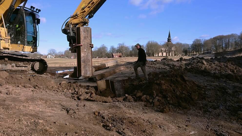 grävskopa och man som utför grundläggningsarbete med klosterkyrkan i barkgrunden