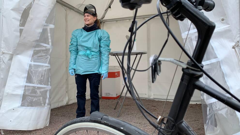 En cykel i förgrunden och en ung kvinna i ett provtagningstält i bakgrunden, hon har skyddskläder på sig.