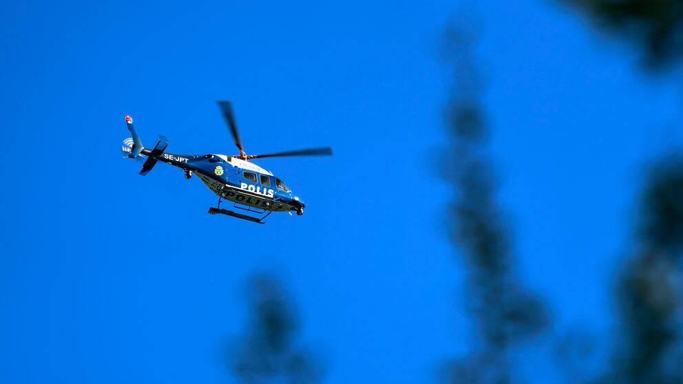 En polishelikopter som flyger mot en blå himmel.