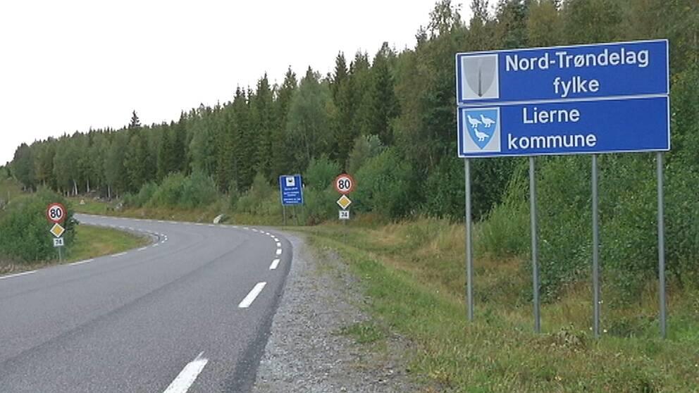 Asfaltsväg och blå vägskylt med texten Nord-Tröndelag fylke och Lierne kommune.