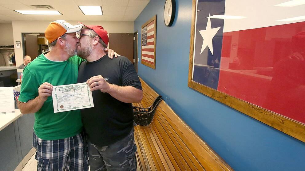 Michael Crow, till vänster, och Robert Woodcock kysser varandra efter att ha fått sin äktenskapslicens i Waco, Texas.