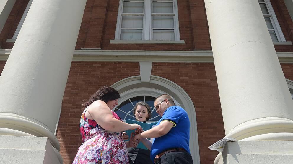 Leah Bloomfield och Courtney Messemore håller varandras händer under deras bröllop i Hattiesburg, Mississipi. De valde att göra det trots att överåklagaren i delstaten varnat för att beslutet kanske inte skulle gå igenom.