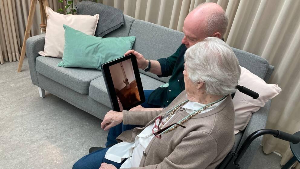 En medelåldersman sitter bredvid en äldre kvinna som sitter i rullstol. Han håller upp en surfplatta och visar ett videoklipp på en bebis.