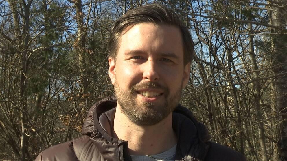 Nicklas står och tittar in i kameran iklädd en brun dunjacka. I bakgrunden syns barrträd.
