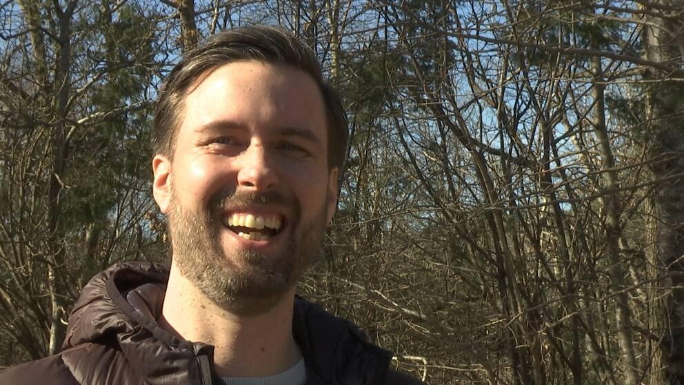 Nicklas Björkman står i en skog och skrattar. Han har en brun dunjacka.
