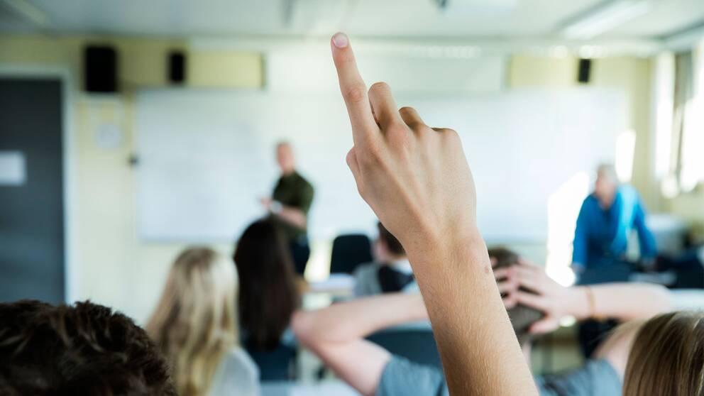 Elever räcker upp handen i ett klassrum