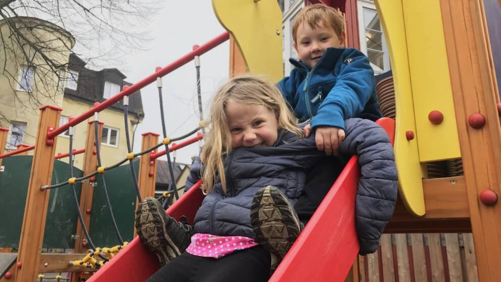två barn i femårsåldern sitter i en rutschkana.