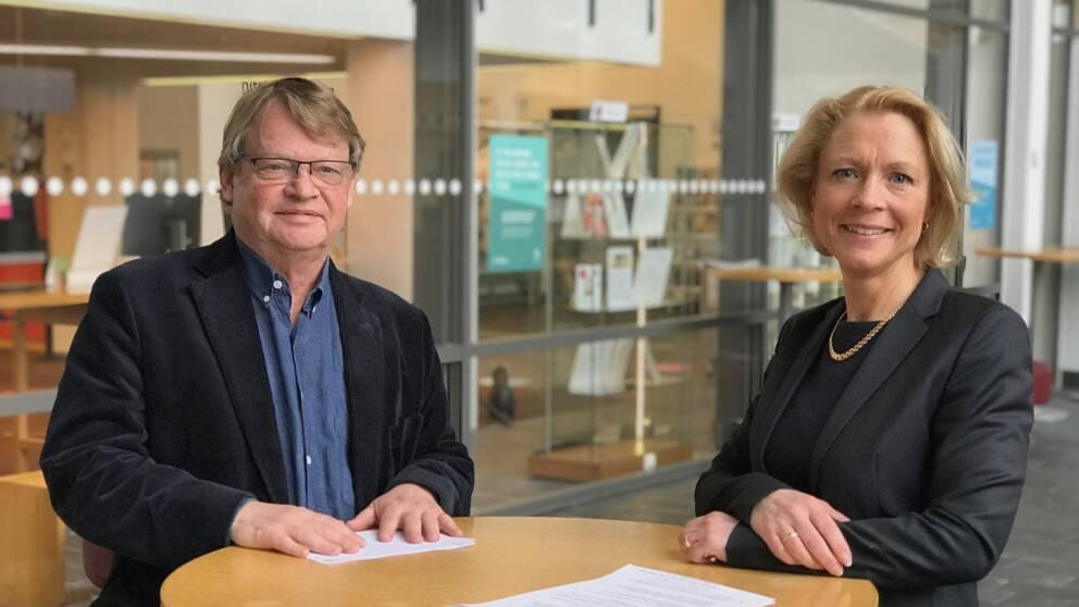 Rolf Solli och Anna Cregård vid ett ståbord framför biblioteket på Högskolan i Borås.
